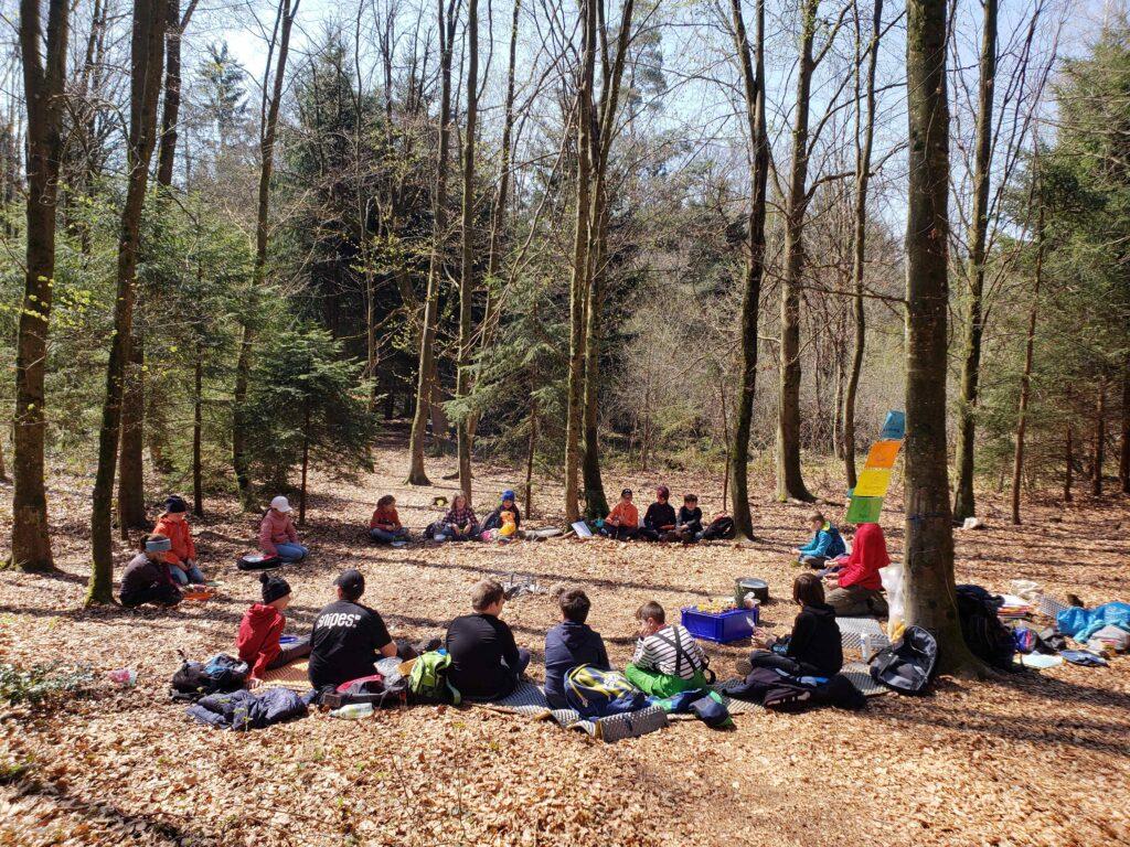 Schulklasse im Kreis im Wald